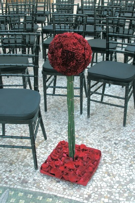 Black chiavari and a red flower arrangement set on bamboo stalks