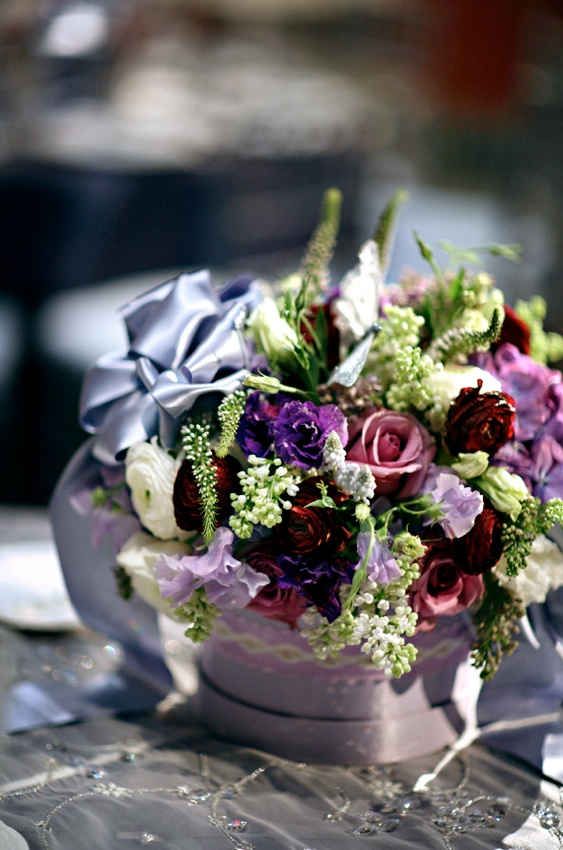 Colorful flowers with a lavender bow in a ribbon wrapped container