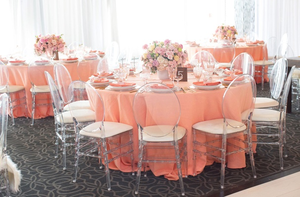 light pink linens clear ghost chairs low pink flower centerpieces bridal shower