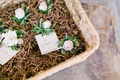 Basket filled with pink rose and green leaf boutonnieres for groomsmen