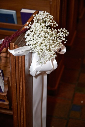 Baby's breath with white satin ribbon on wood church pew wedding ceremony