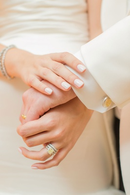 Bride in neutral manicure nails with yellow diamond engagement ring and groom's yellow gold band