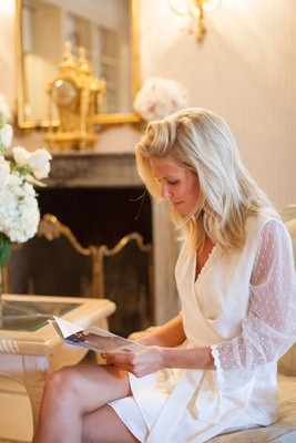 bride in white robe and natural hair reading a card from groom before getting hair and makeup done