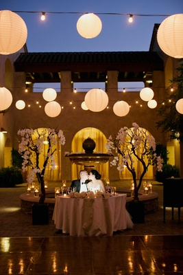 bride and groom kiss at sweetheart table, trees frame sweetheart table, paper lanterns
