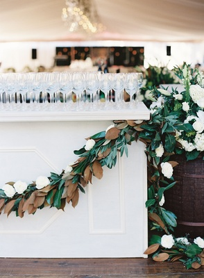 White bar with wine glasses on top decorated with magnolia leaf garland and white flower wine barrel