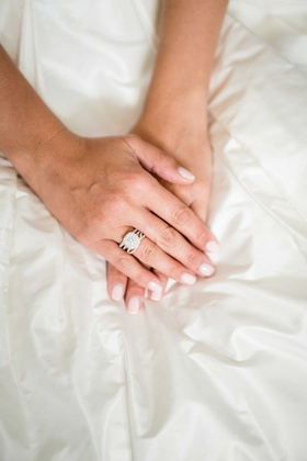 double halo engagement ring on bride's hand with light manicure nails