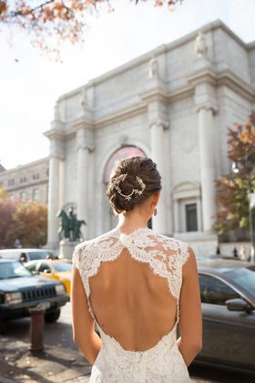 Bride in a lace key-hole gown by Monique Lhuillier and updo with sparkling band