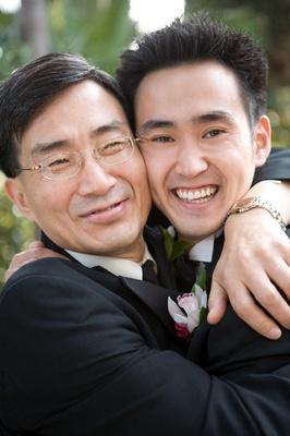 Father and son hug on wedding day