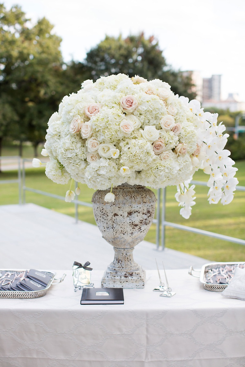 White orchid hydrangea rose flower arrangement in urn guest book and programs on trays