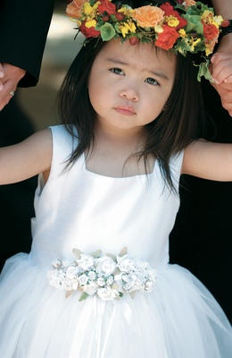 Flower girl in white dress with colorful flower crown