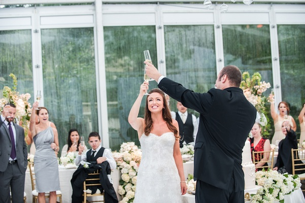 Groom in black tuxedo toasts with bride in a strapless lace Monique Lhuillier gown in glass tent