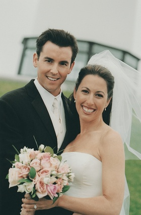 Groom with white tie and vest and bride with pink bouquet