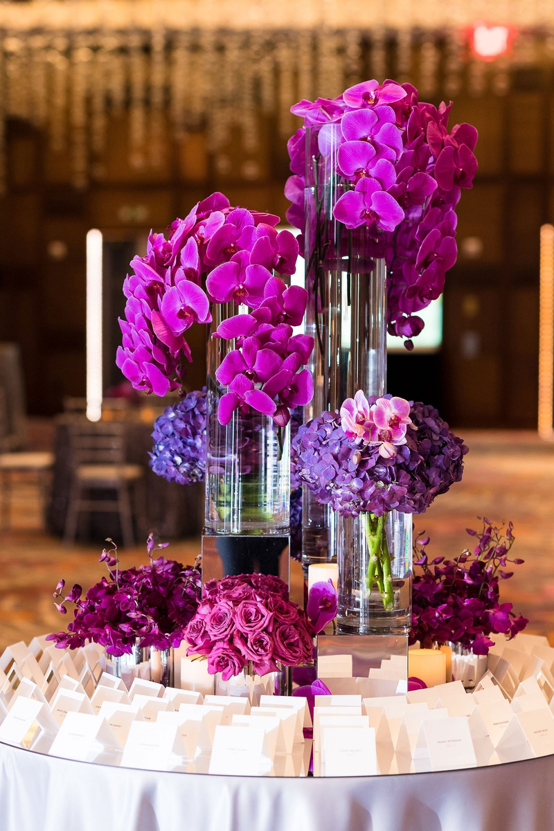 escort card table with fuchsia flowers, orchids, purple orchids