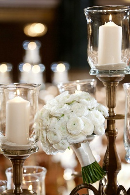 Wedding bouquet next to candles with white ranunculus wrapped with ivory ribbon