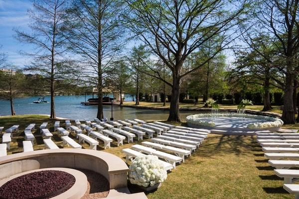 White benches on grass arranged around podium