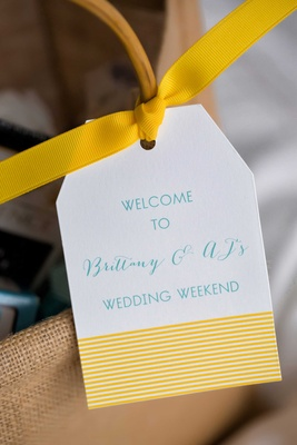 Yellow and blue welcome bag tag for wedding weekend tied with bright yellow grosgrain bow