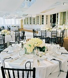 white tablecloths and flower arrangements with black chairs