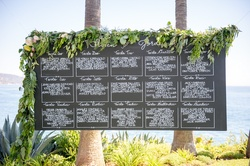 Oceanfront wedding reception with chalkboard seating chart with greenery, white, pink flowers