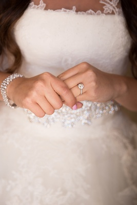 close up picture of brides engagement ring and crystal bracelet