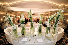 Ivory and white flowers and linens in ballroom