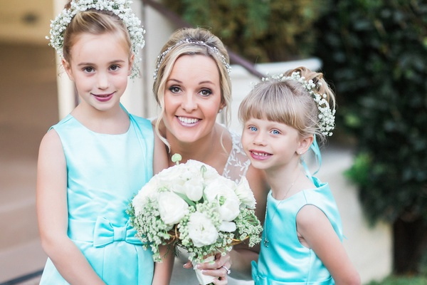Bride with flower girls in sleeveless Tiffany blue satin dresses with a bow, baby's breath halos