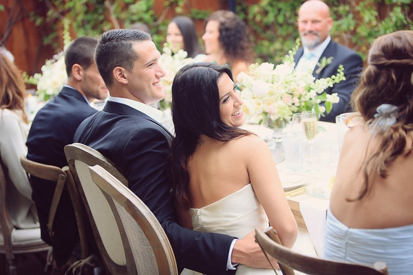 bride and groom smile at reception table