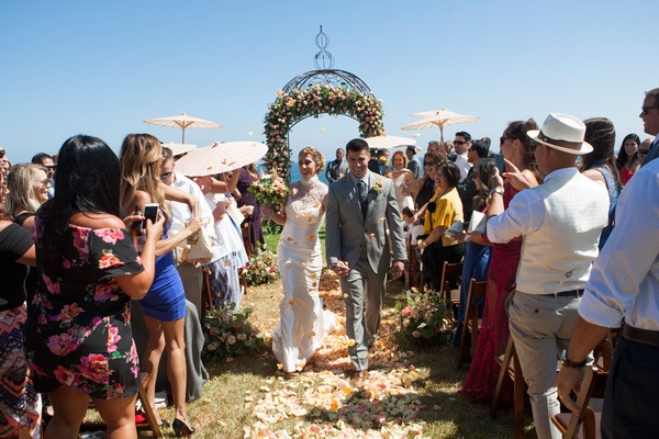 Bride in Ines Di Santo wedding dress holding groom's hand up aisle outdoor summer wedding parasols