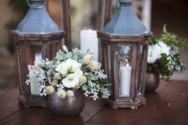 Ranch wedding reception with white flowers, greenery in coppertone vases, wood lanterns