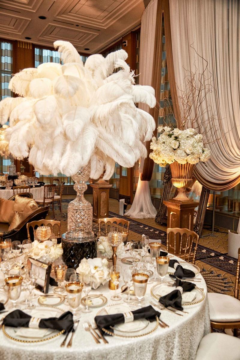 Glam vintage inspired wedding reception white linen black bow napkin white feather tall centerpiece