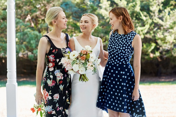 bride in classic wedding dress with mother of bride in flower print dress and sister in blue dress