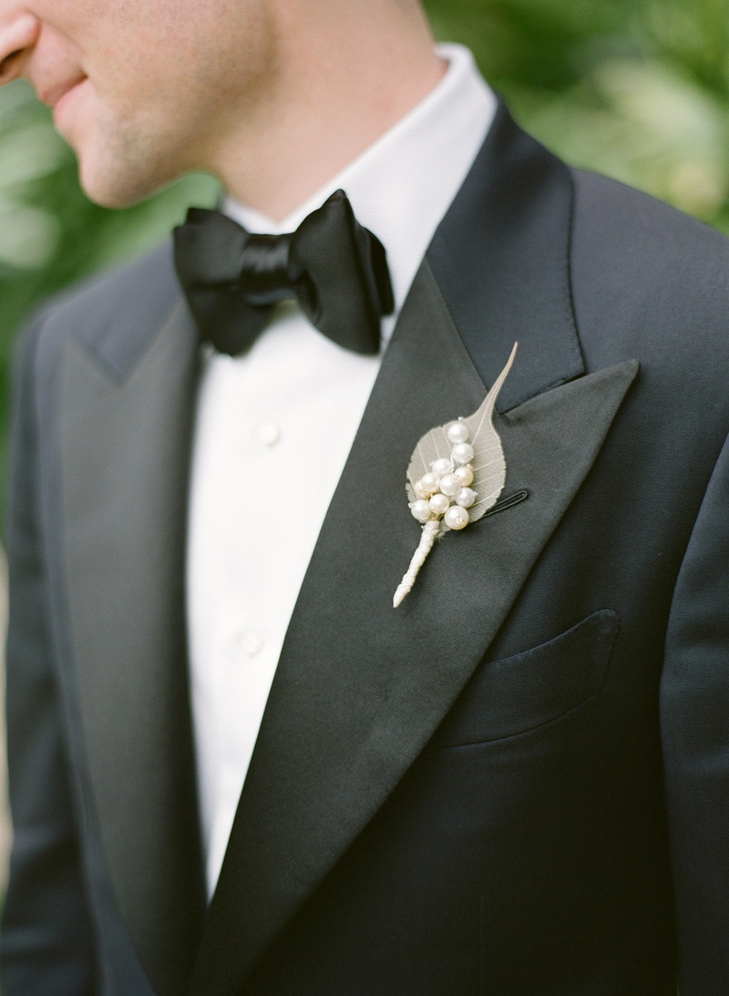 Groom in tuxedo and bow tie with pearls on lapel