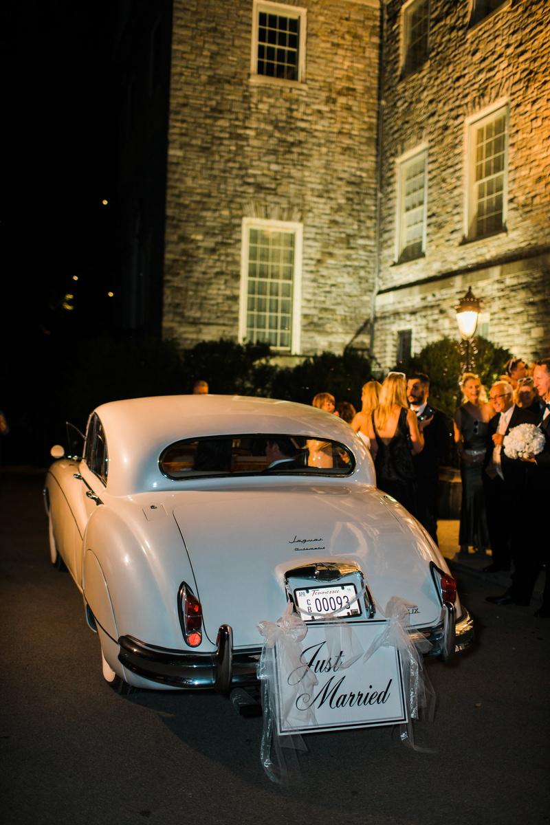 "white vintage jaguar getaway car with ""just married"" sign"