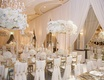 opulent wedding reception with ivory and gold, floral arrangements on tall gold stands