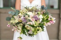 full, wide bridal bouquet with different shades of greenery with blush flowers and lilac accents