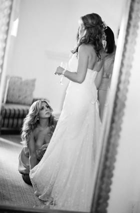 Black and white photo of bridesmaid helping bride with her dress