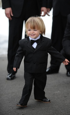 Young blond ringbearer in black tux with bow tie