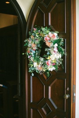 wedding ceremony wood door wreath with greenery pink flowers orange yellow white blooms