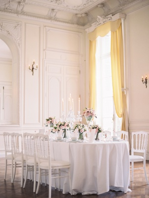 Wedding reception table at white ballroom of the Chateau de Santeny with floor-to-ceiling window