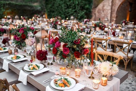 king's tables with small arrangements of greenery, burgundy and pink roses, cream table runner