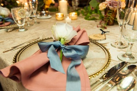 Wedding reception pattern linen with single rose flower at each guest place setting