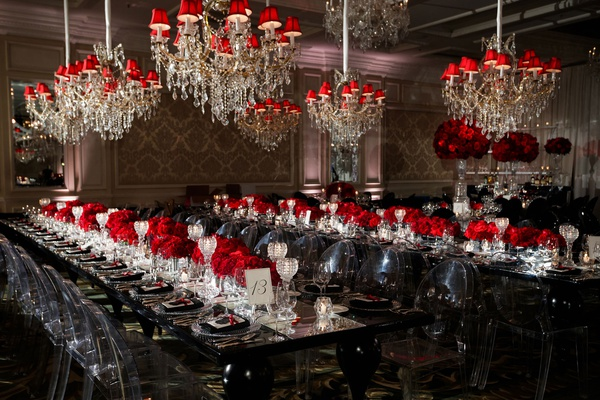 wedding reception long black table clear chairs chandelier red shades red rose flowers crystal