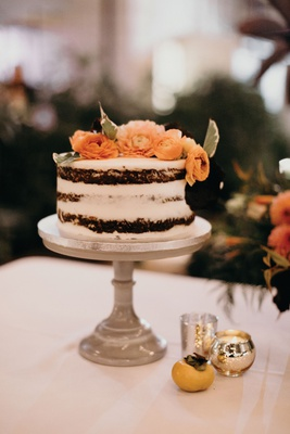Small semi-naked wedding cake with fresh orange flowers on top ranunculus green leaves cake stand