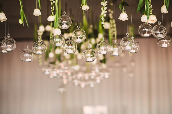 small white flowers hanging from ceiling with suspended glass orbs holding tiny candles