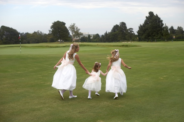 Three girls in white dresses with pink sashes