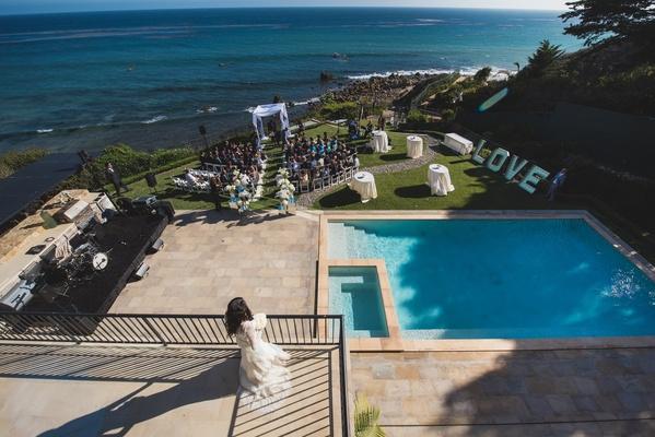 bride on balcony overlooking oceanside ceremony venue
