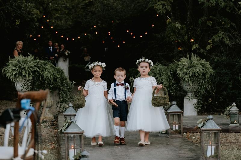 two cute flower girls white dresses moss baskets ring bearer in suspenders high socks bow tie