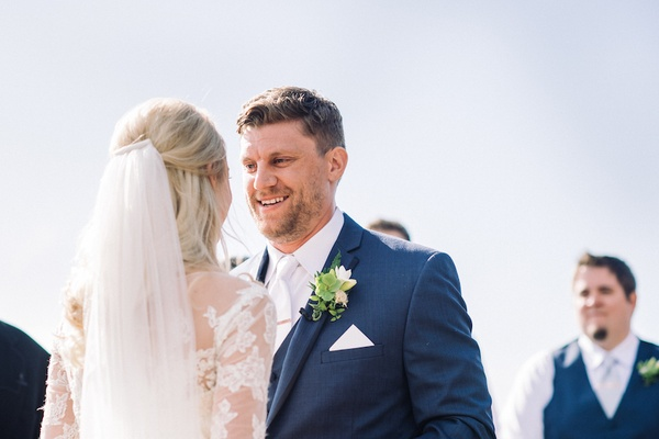 Groom smiling at bride in navy blue suit at wedding