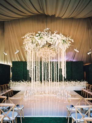 Wedding ceremony white flooring flower chandelier with garlands of orchids and crystals at altar