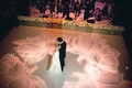 Flower design projected in pink on wedding dance floor