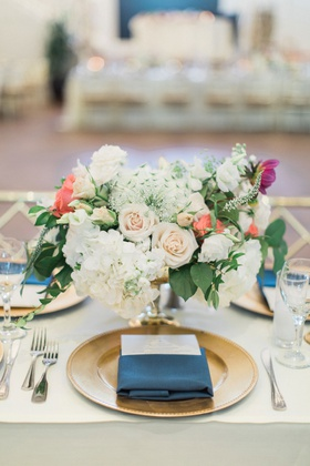 Wedding reception table gold charger plate navy blue napkin menu low flower arrangement hydrangea